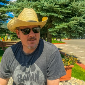 A picture of me enjoying the sun in a straw cowboy hat, sunglasses and Batman T-shirt